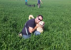 איש וכלב מאושרים מתחבקים בשדה ירוק בחוות הכלבים של דרור- אילוף כלבים, פנסיון כלבים